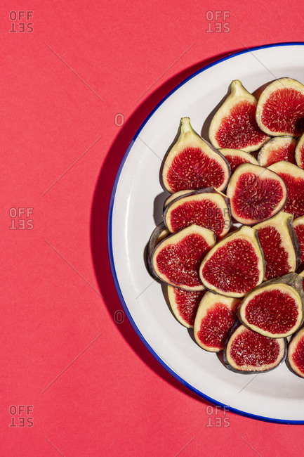 Directly above shot of fig slices arranged in plate over red background