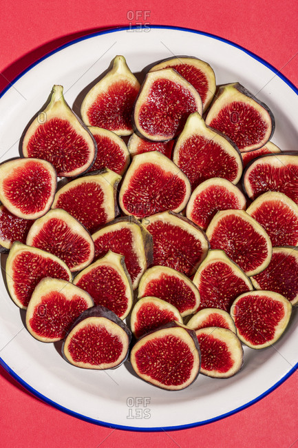 Directly above shot of fig slices arranged in plate on red background