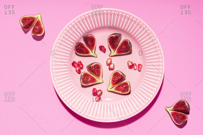 Directly above shot of fig slices arranged in plate over pink background