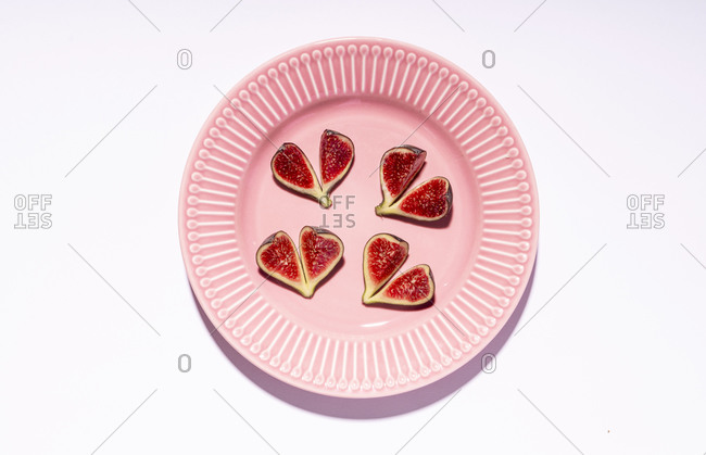 Directly above shot of fig slices arranged in plate over white background