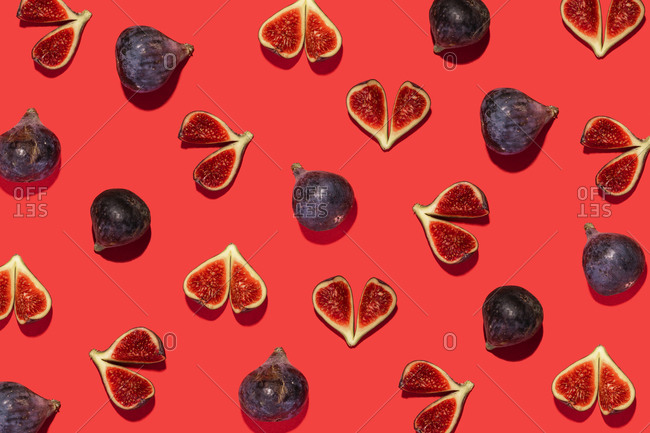 Directly above shot of fig fruit arranged on red background