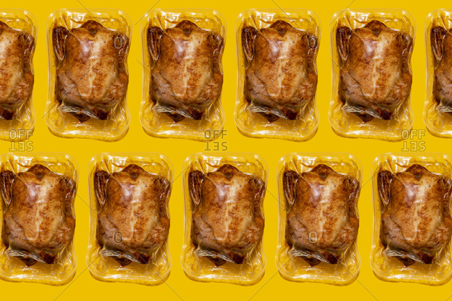 Vacuum packed roasted chickens on yellow background
