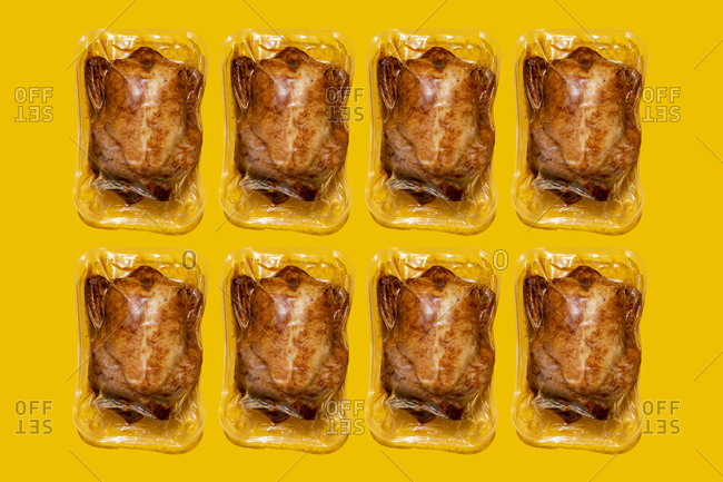 Vacuum packed roasted chickens arranged in a row on yellow background