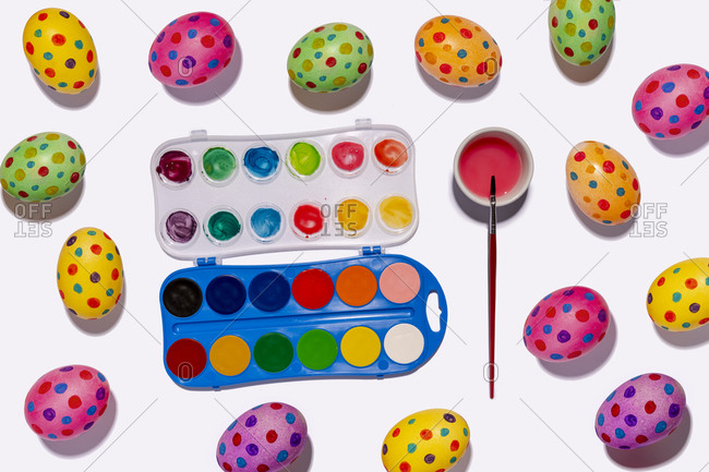 Watercolor paints and colorful spotted Easter eggs