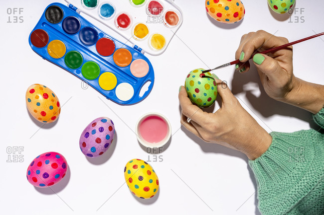 Hands of woman painting Easter eggs with colorful watercolors