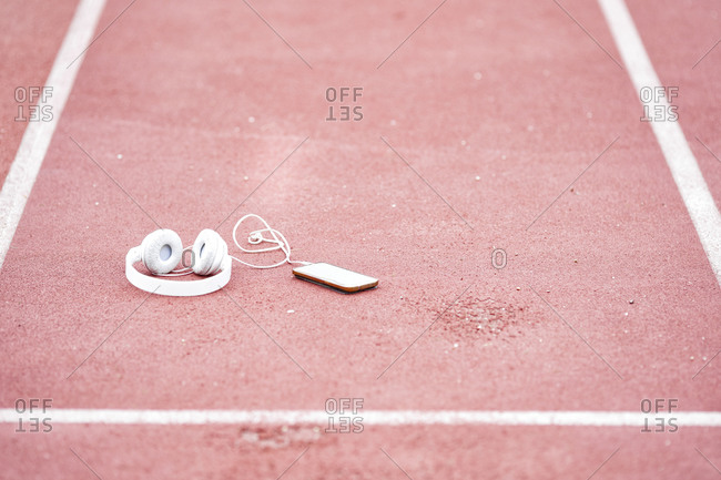 Smart phone and headphones on red running track