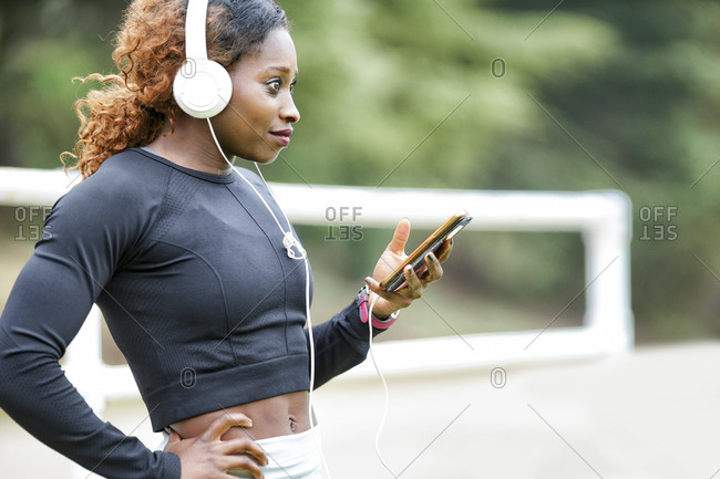 Sportswoman with hand on hip looking away using smart phone standing outdoors