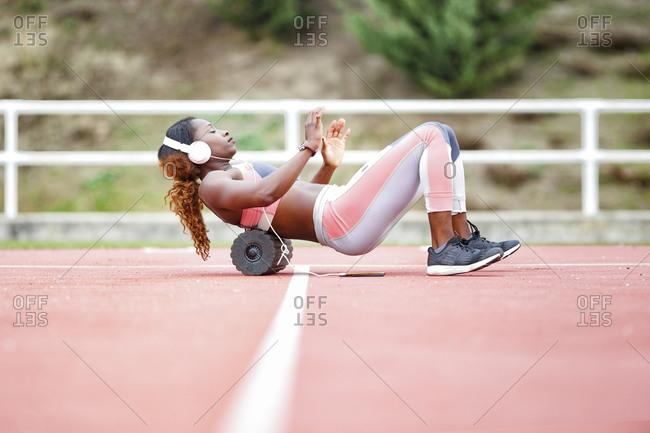 Female athlete exercising on foam roller while listening music