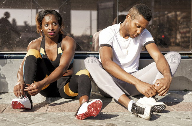 Athletes tying shoelaces while sitting on sidewalk at city