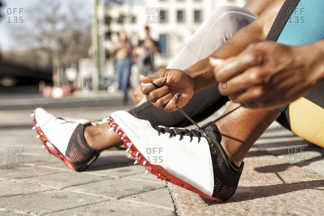 Sportswoman typing shoelace while sitting by man on sidewalk at city