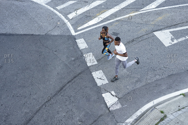 Couple running on road together at city
