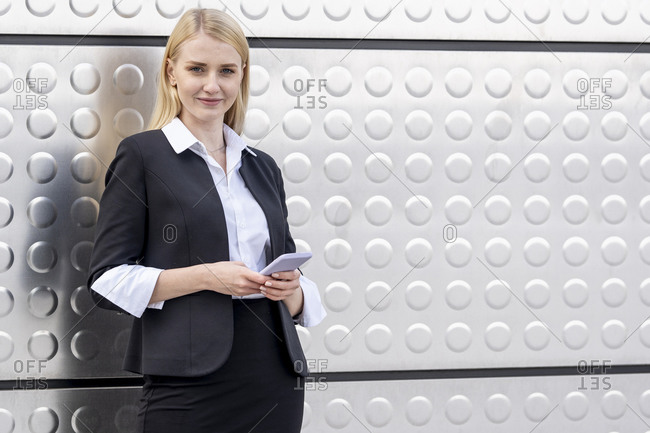 Blond businesswoman using mobile phone while standing against silver wall