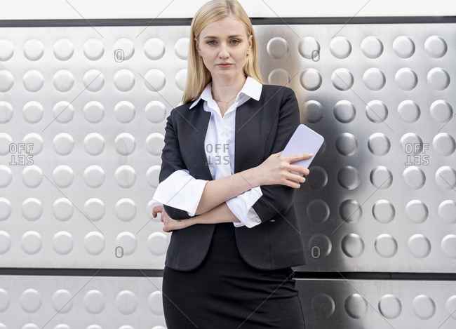 Confident businesswoman holding mobile phone while standing with arms crossed against silver wall