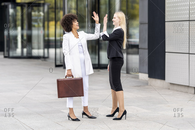 Businesswomen giving high five while standing on footpath