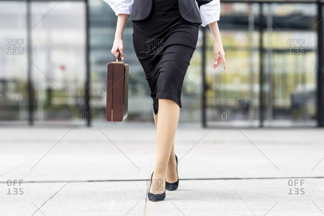 Young businesswoman wearing high heels walking with briefcase on footpath