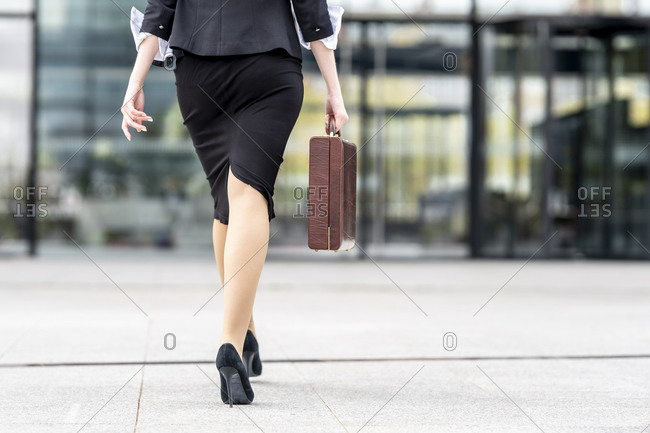 Businesswoman wearing high heels walking with briefcase on footpath