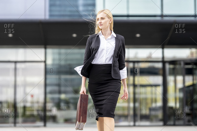 Businesswoman holding briefcase while walking against building