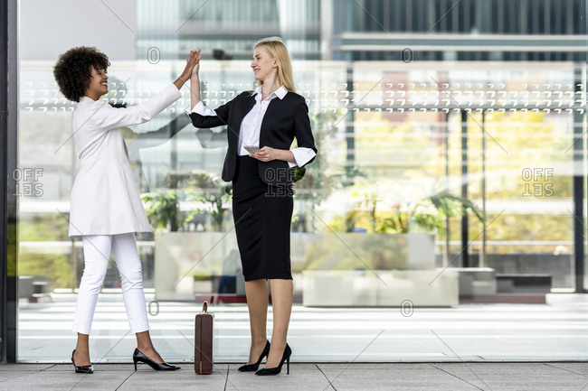 Businesswoman with mobile phone giving high five to colleague while standing against glass wall