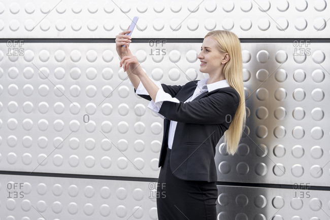 Blond businesswoman taking selfie through mobile phone while standing against silver wall
