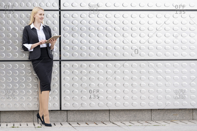 Smiling woman using digital tablet while standing against silver wall