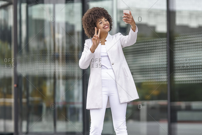 Smiling businesswoman showing peace gesture while taking selfie through mobile phone against outdoors