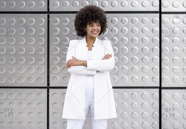 Confident businesswoman standing with arms crossed against silver wall