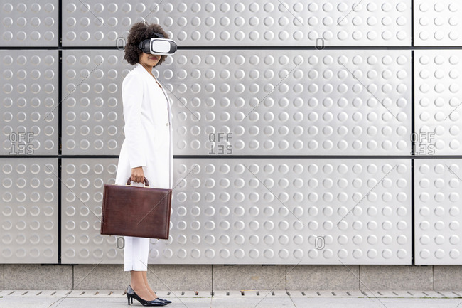 Businesswoman with briefcase using virtual reality glasses while standing against silver wall