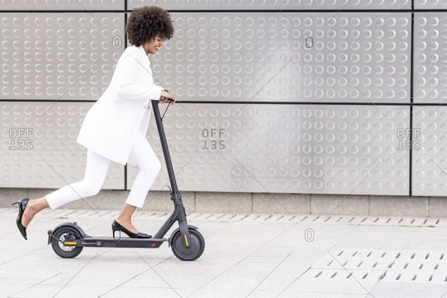 Smiling businesswoman riding electric push scooter against silver wall