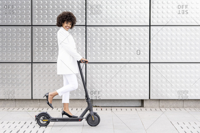 Businesswoman smiling while riding electric push scooter against silver wall