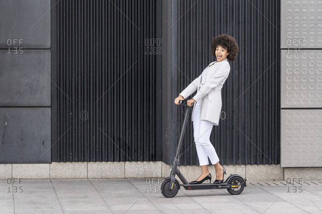 Excited businesswoman riding electric push scooter against wall