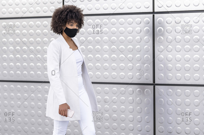 Businesswoman wearing face mask while walking against silver wall