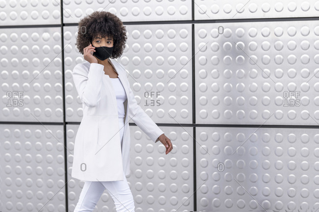 Businesswoman wearing face mask using mobile phone while walking against silver wall