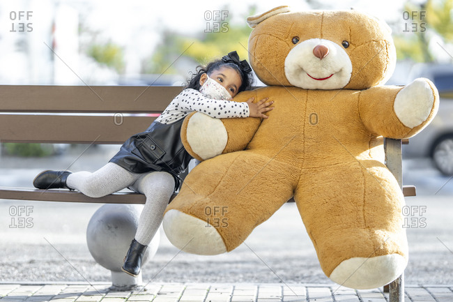 Girl wearing face mask embracing teddy bear while sitting on bench