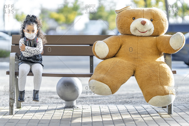Girl wearing face mask sitting with teddy bear at social distance on bench