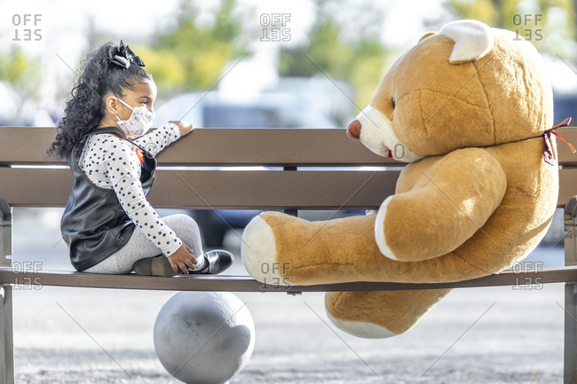 Girl wearing face mask playing with teddy bear while sitting on bench