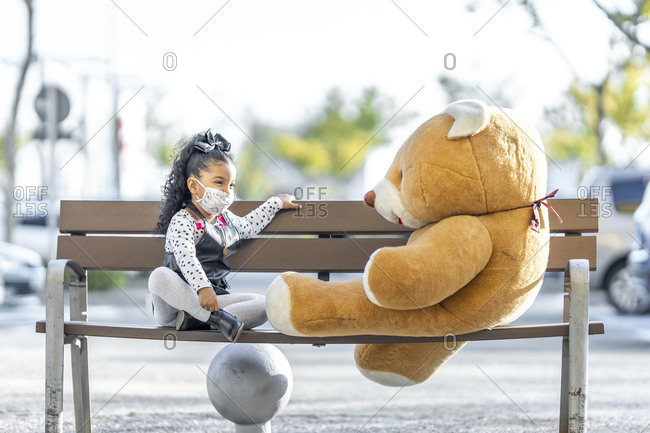 Girl wearing face mask playing with teddy bear while sitting at social distance on bench