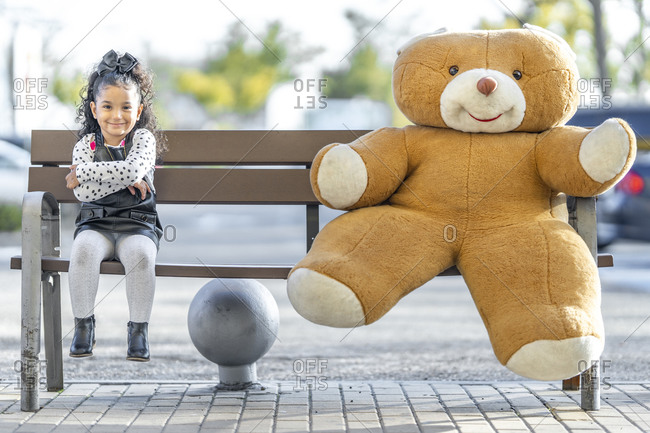 Smiling girl sitting with arms crossed by teddy bear at social distance on bench