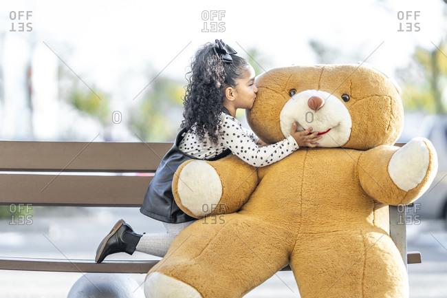Girl kissing teddy bear while kneeling on bench