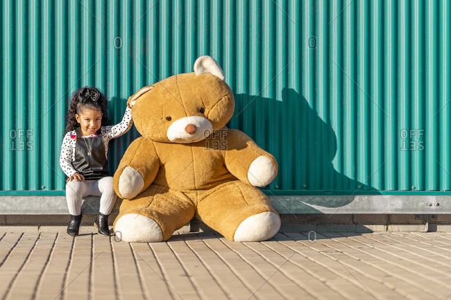 Cute girl paying with teddy bear while sitting against green wall