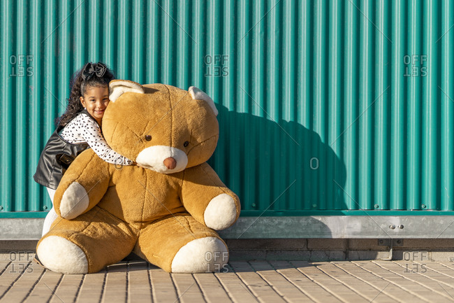 Cute girl embracing teddy bear while standing against green wall