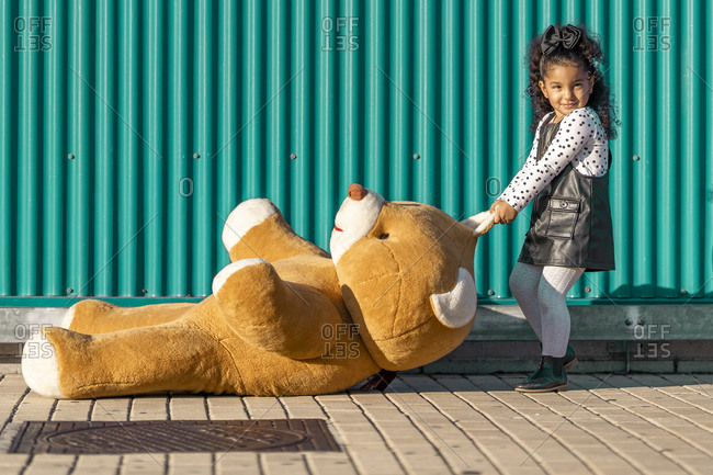 Girl dragging teddy bear on footpath while standing against green wall