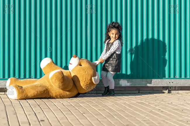 Girl dragging teddy bear on footpath while playing against green wall
