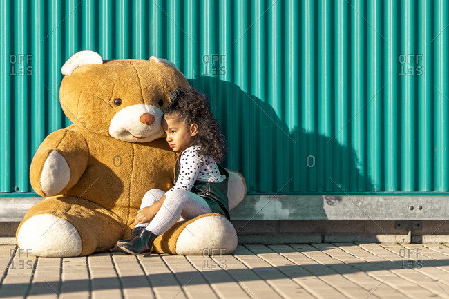 Girl embracing while sitting with teddy bear against green wall