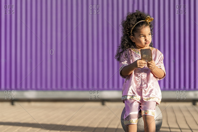Girl doing pout while using mobile phone against purple wall