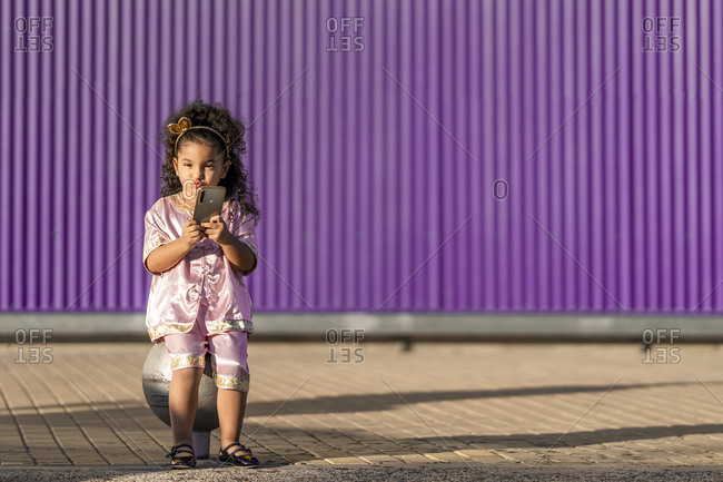 Cute girl doing pout while using mobile phone against purple wall