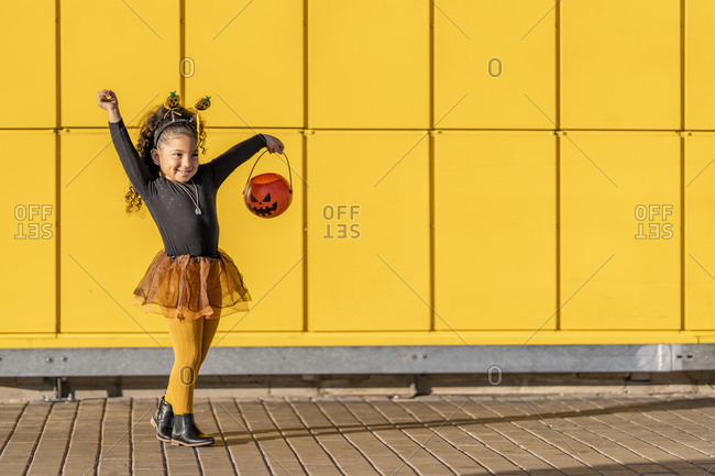 Smiling girl dancing with Halloween flower pot and headband against yellow checked pattern wall