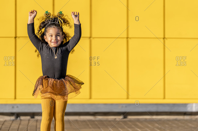 Cute girl wearing Halloween headband dancing while standing against yellow checked pattern wall