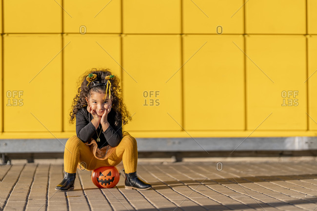 Girl sitting with head in hands on Halloween flower pot against yellow checked pattern wall