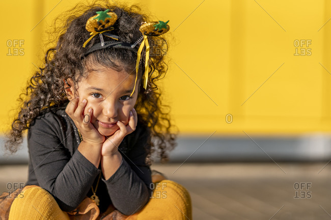 Girl sitting with head in hands against yellow wall