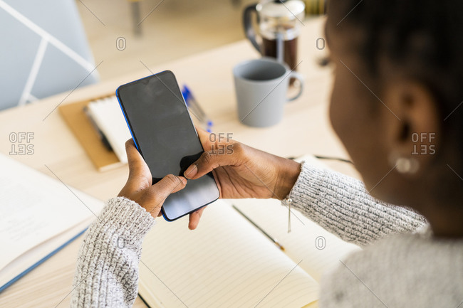 Young woman using smart phone while sitting at home